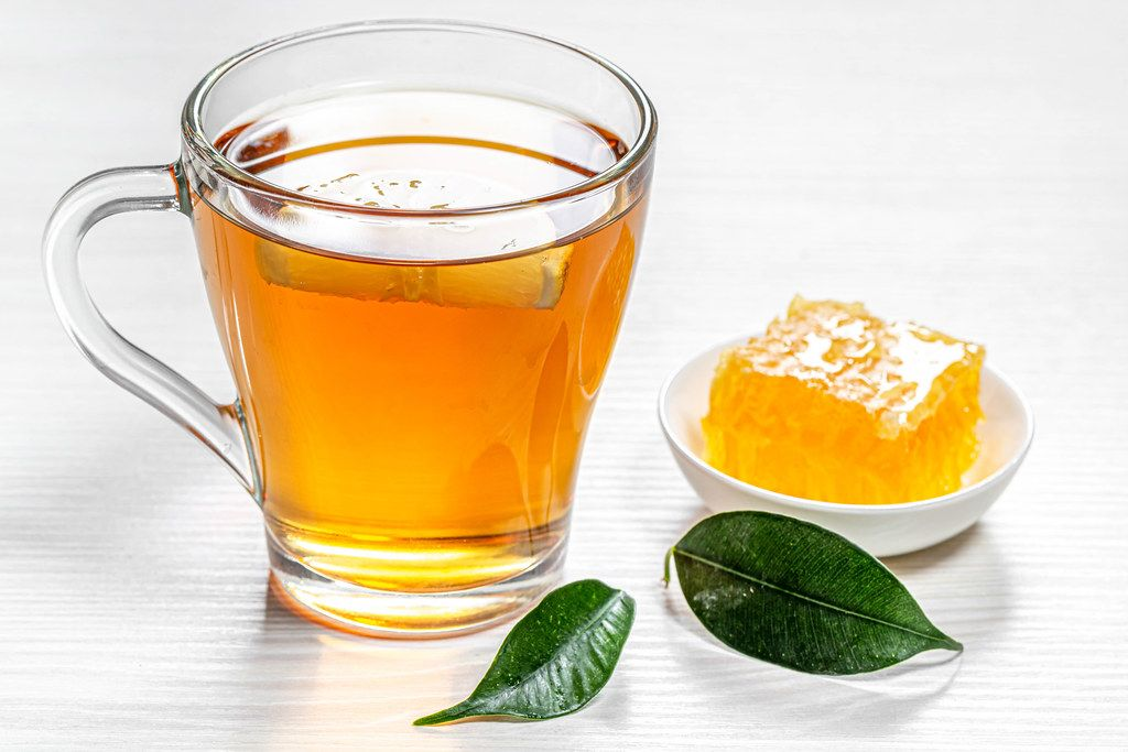 Cup of hot tea with green leaves and honeycomb