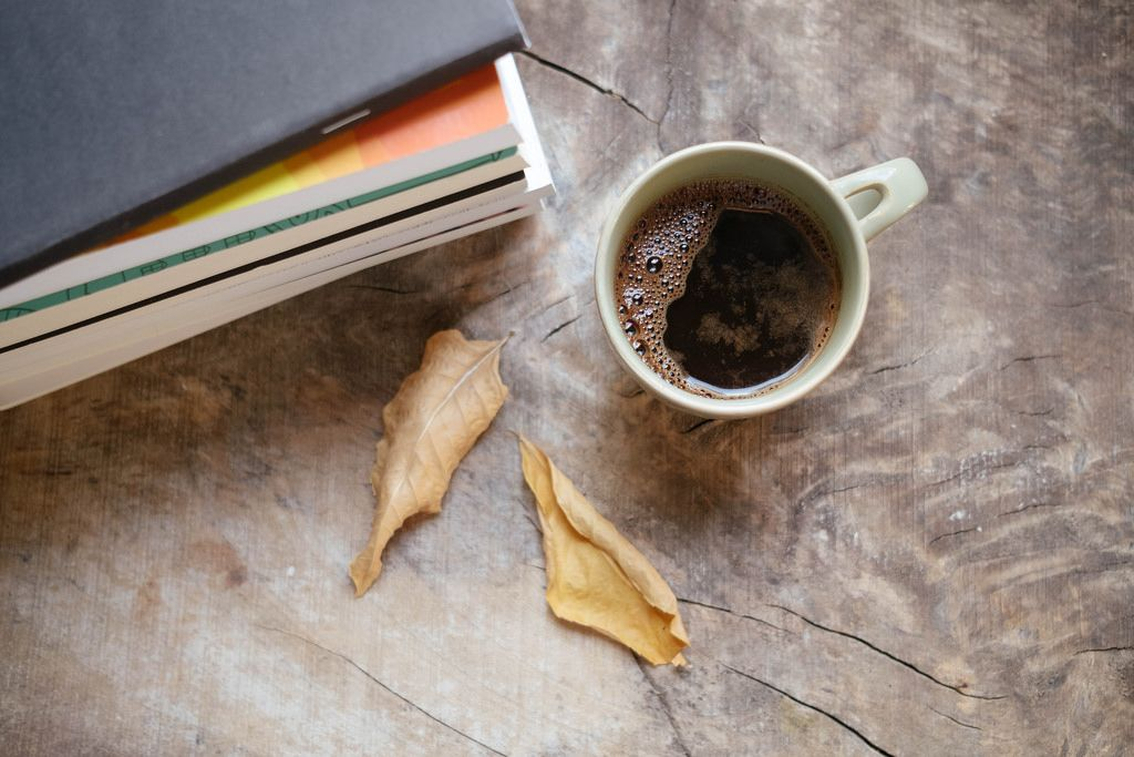 Cup of warm dark coffe and books on a rustic table