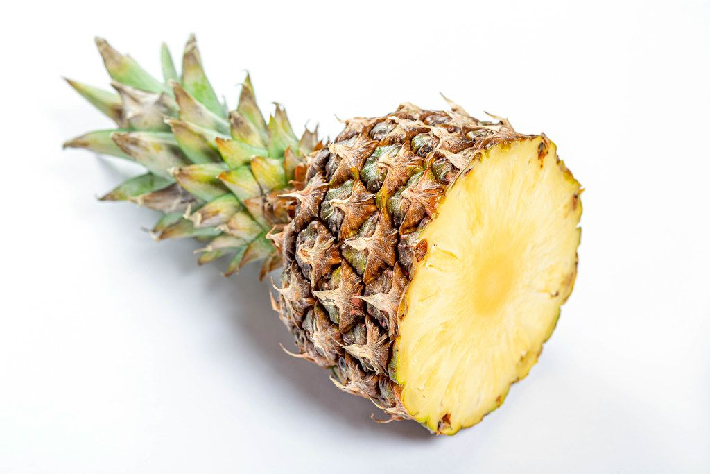 Cut ripe pineapple on white background
