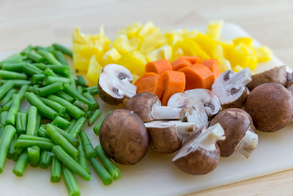 Cutting vegetables for oven-roasted vegetables: green beans, carrots, yellow bell pepers and mushrooms