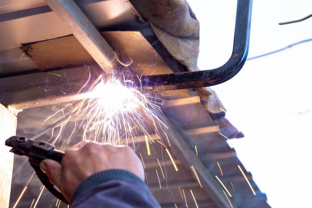 Dachreperaturen werden durch einen Schweißer mit Elektroden durchgeführt