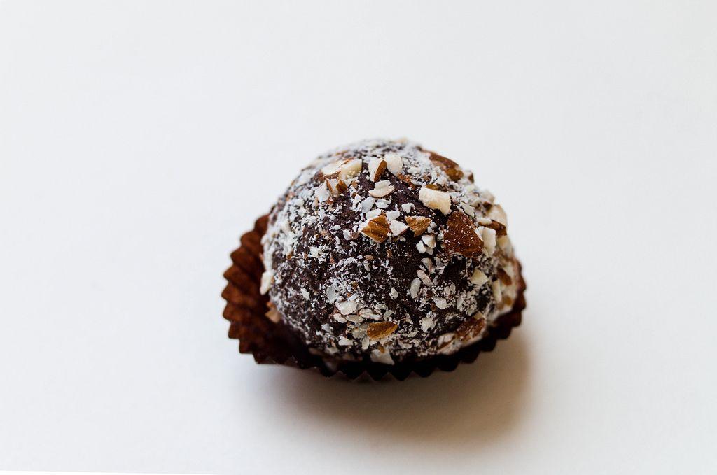 dark chocolate truffle with cocoa powder and chopped hazelnut