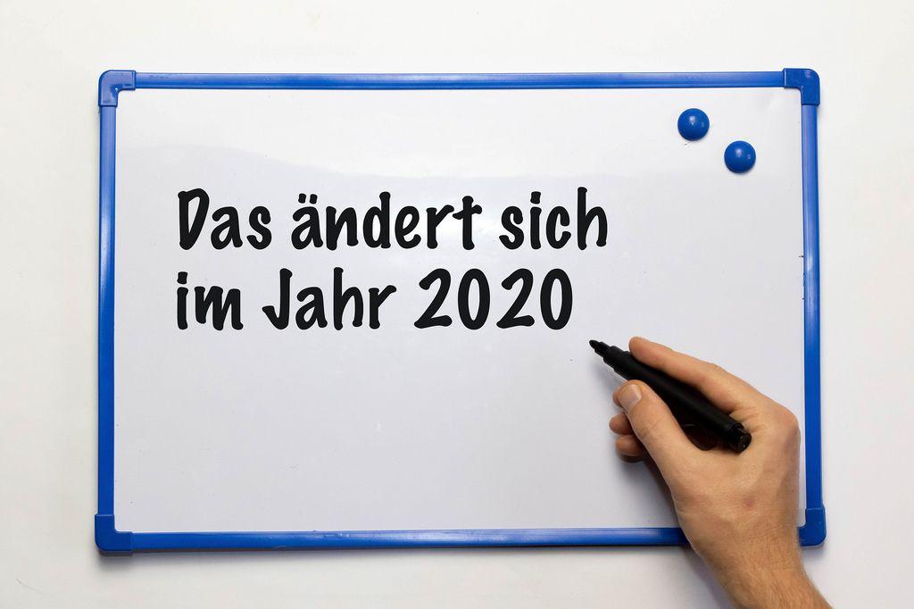 Das ändert sich im Jahr 2020: Schrift auf Whiteboard mit blauen Rahmen und blauen Magneten - Nahaufnahme in Frontalansicht