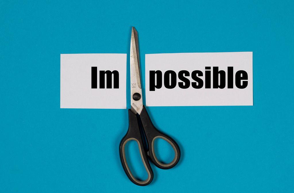 Das Wort Impossible auf einem durchgeschnittenem Papier mit Schere auf blauem Hintergrund