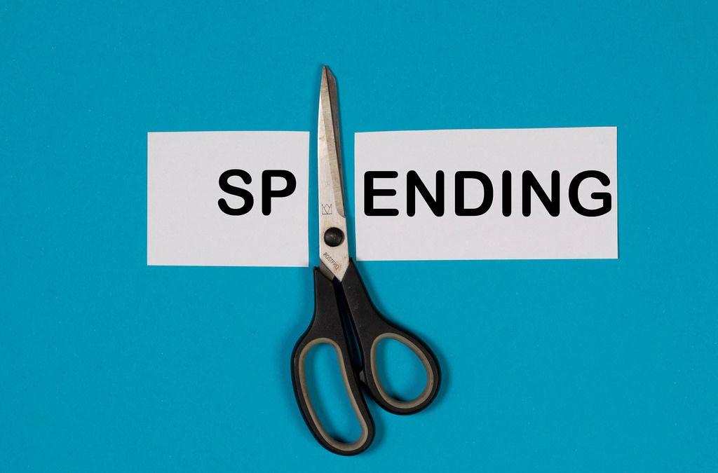 Das Wort Spending auf einem durchgeschnittenem Papier mit Schere auf blauem Hintergrund