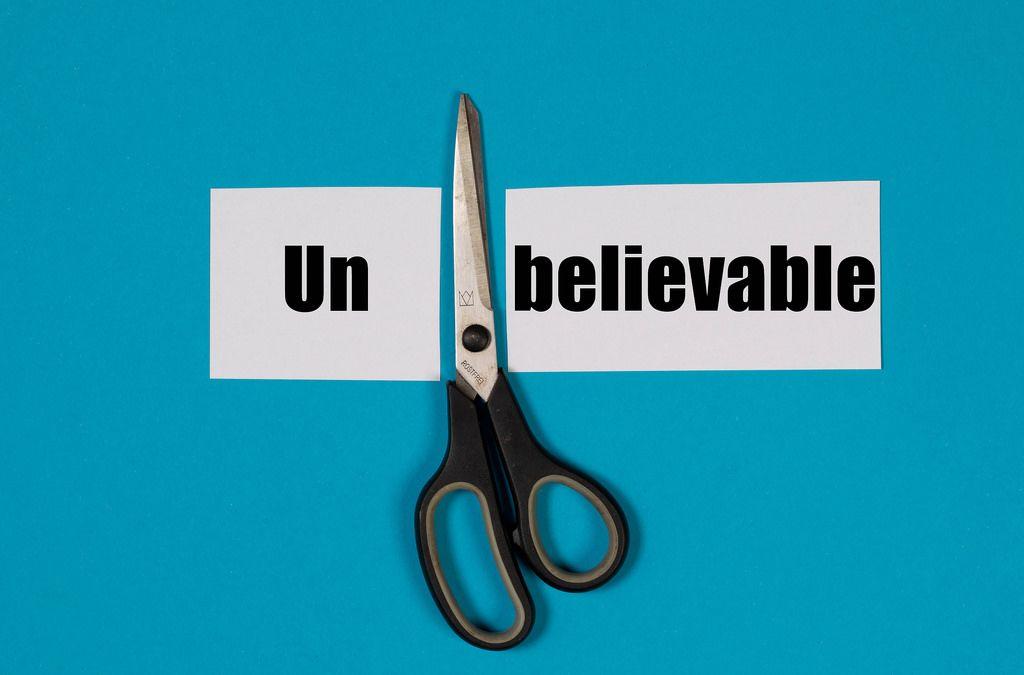 Das Wort Unbelievable auf einem durchgeschnittenem Papier mit Schere auf blauem Hintergrund