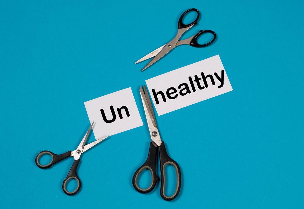 Das Wort Unhealthy auf einem durchgeschnittenem Papier mit Scheren auf blauem Hintergrund