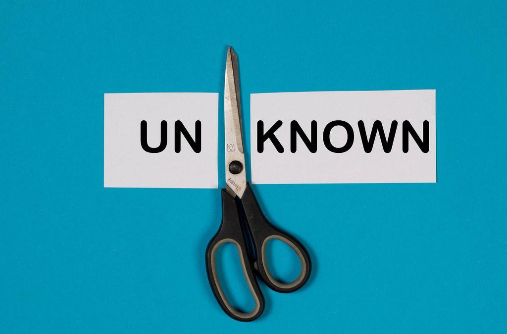 Das Wort Unknown auf einem durchgeschnittenem Papier mit Schere auf blauem Hintergrund