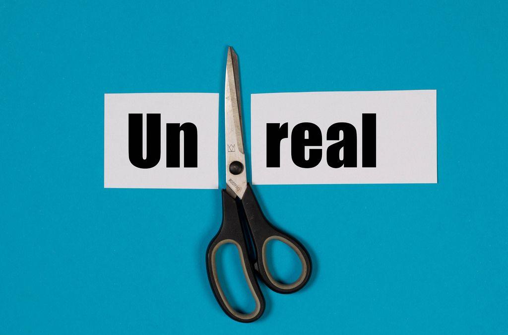 Das Wort Unreal auf einem durchgeschnittenem Papier mit Schere auf blauem Hintergrund