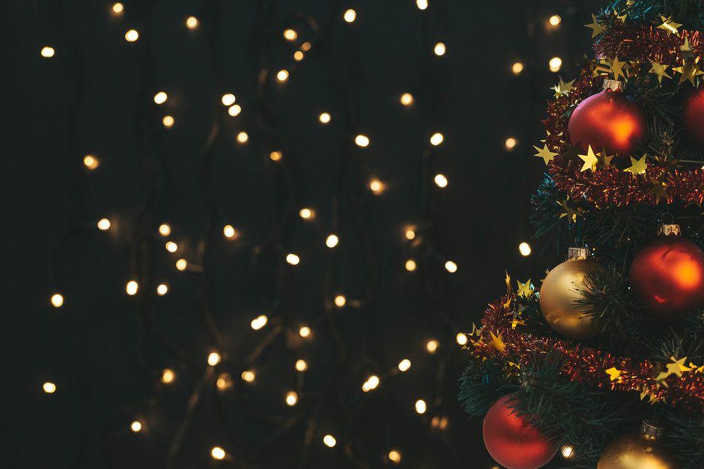 Decorated Christmas tree and luminous garland behind