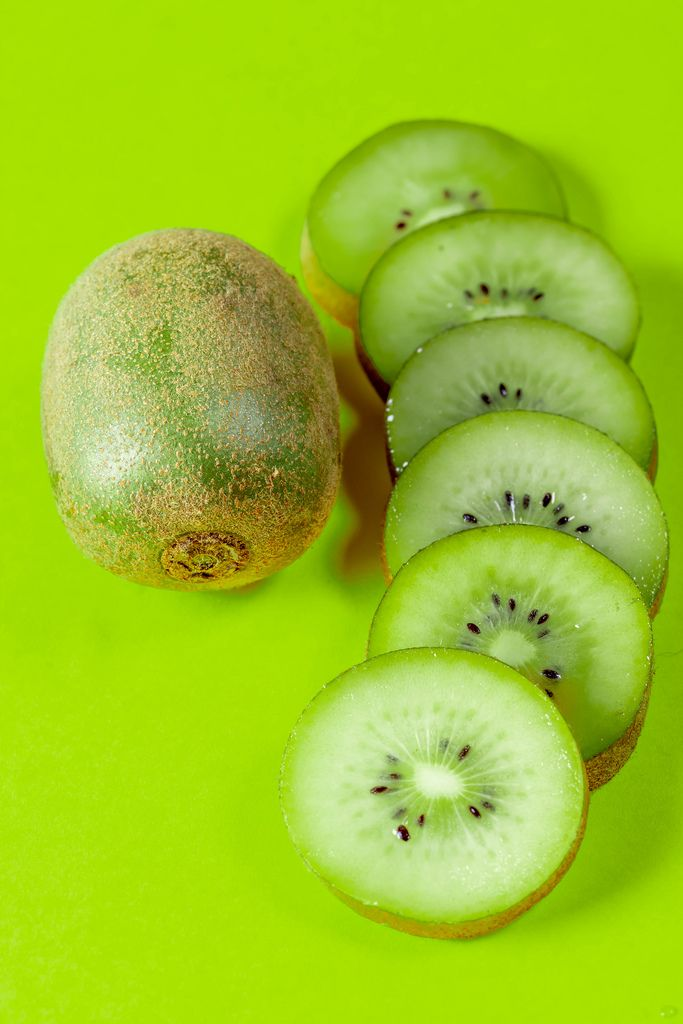 Delicious and healthy kiwi fruit on green background