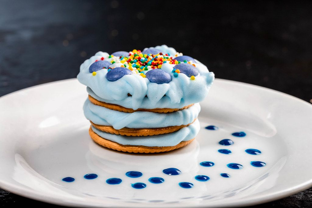 Delicious dessert with blue cream on a white plate (Flip 2019)