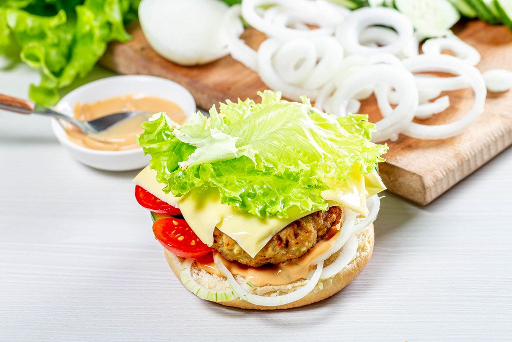 Delicious fresh homemade burger with lettuce, cheese, onion and tomato on a white wooden background (Flip 2019)