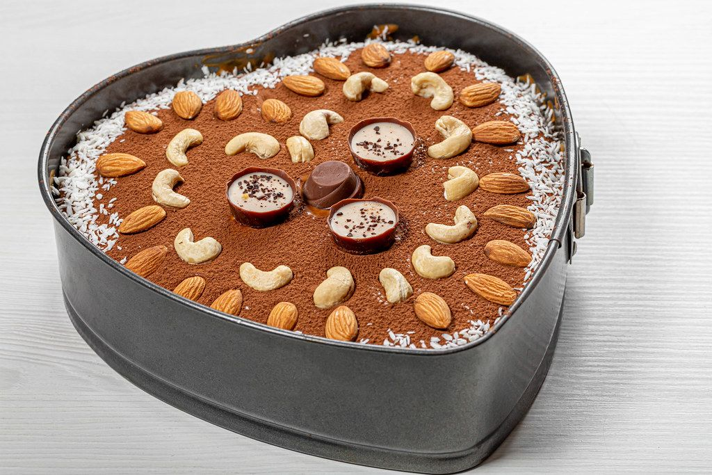 Delicious homemade chocolate cake with heart shaped nuts on white wooden background (Flip 2019)