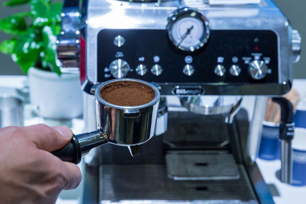 De'Longhi Premium Barista Espresso Machine: Man holding ground coffee in front of Pump Espresso Screen Carrier EC9335.R - La Specialista