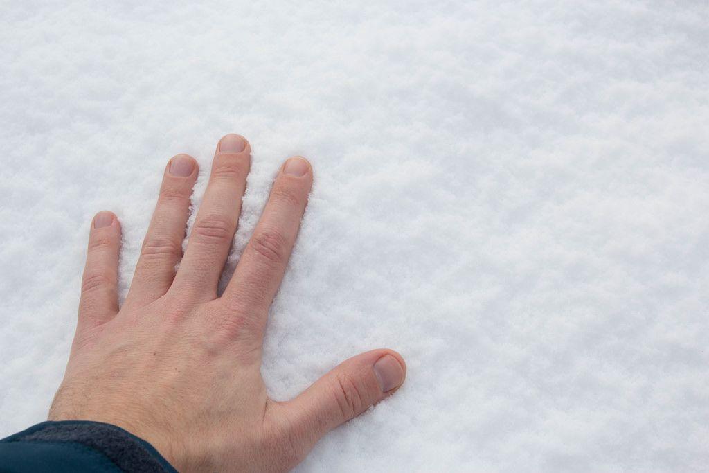 Den Schnee mit der Hand berühren