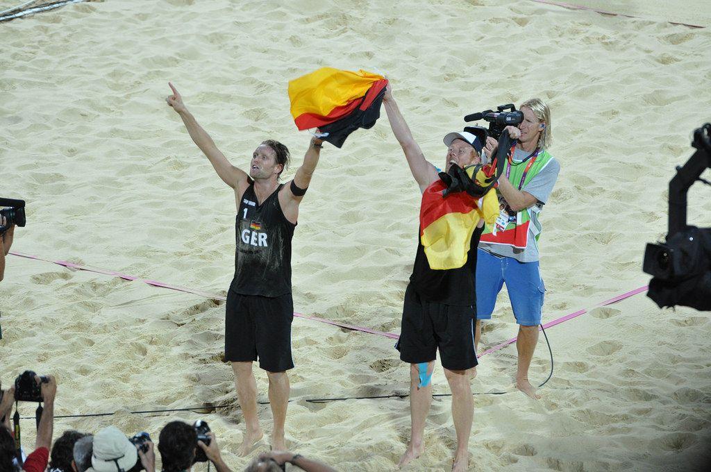 Deutsche Beach-Volleyball-Spieler mit deutscher Flagge in Händen