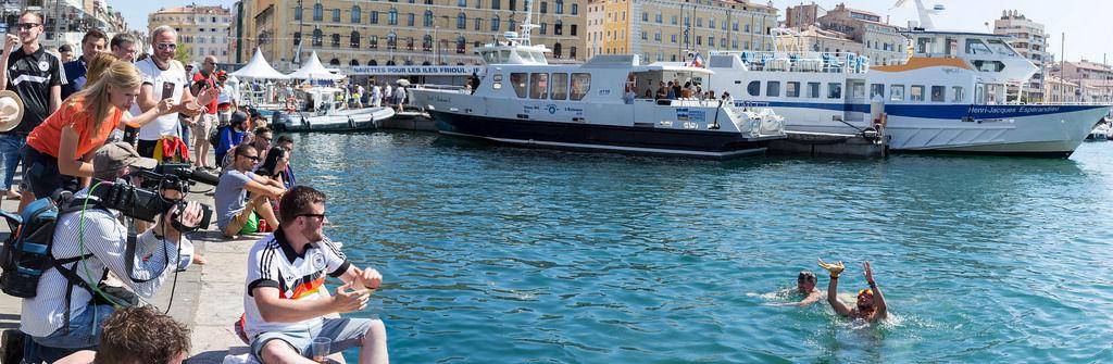 Deutsche Fans schwimmen im alten Hafen von Marseille