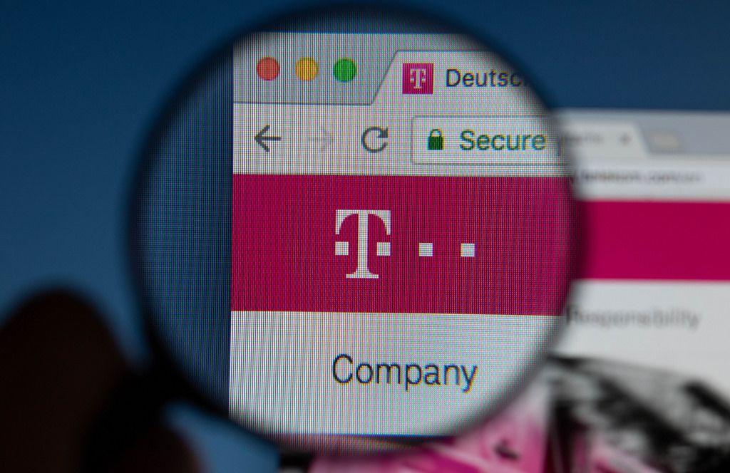 Deutsche Telekom Logo am PC-Monitor, durch eine Lupe fotografiert