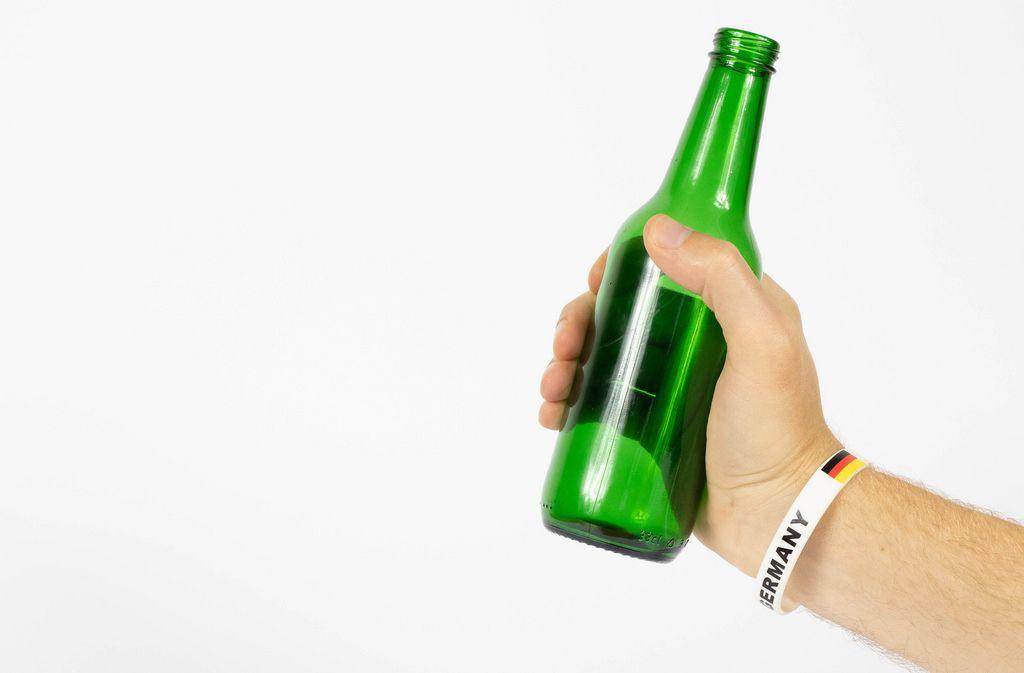 Deutscher Fußball-Fan hält Bierflasche in der Hand