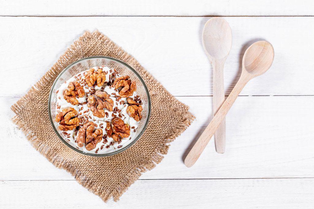 Diät-Dessert mit Walnüssen auf Leinentuch und Holzlöffel auf weißem Holztisch