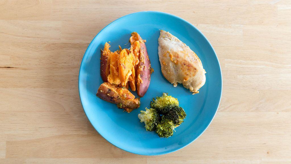 Diät Mahlzeit - Hühnerbrust mit Broccoli und Süßkartoffeln auf einem blauen Teller