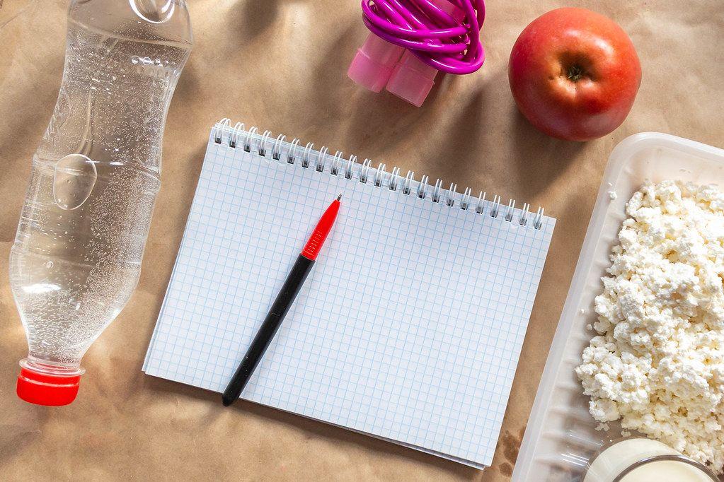 Diät planen mit der Erstellung eines Essensplan, Springseil, Wasserflasche und Apfel als gesundes Lebensmittel