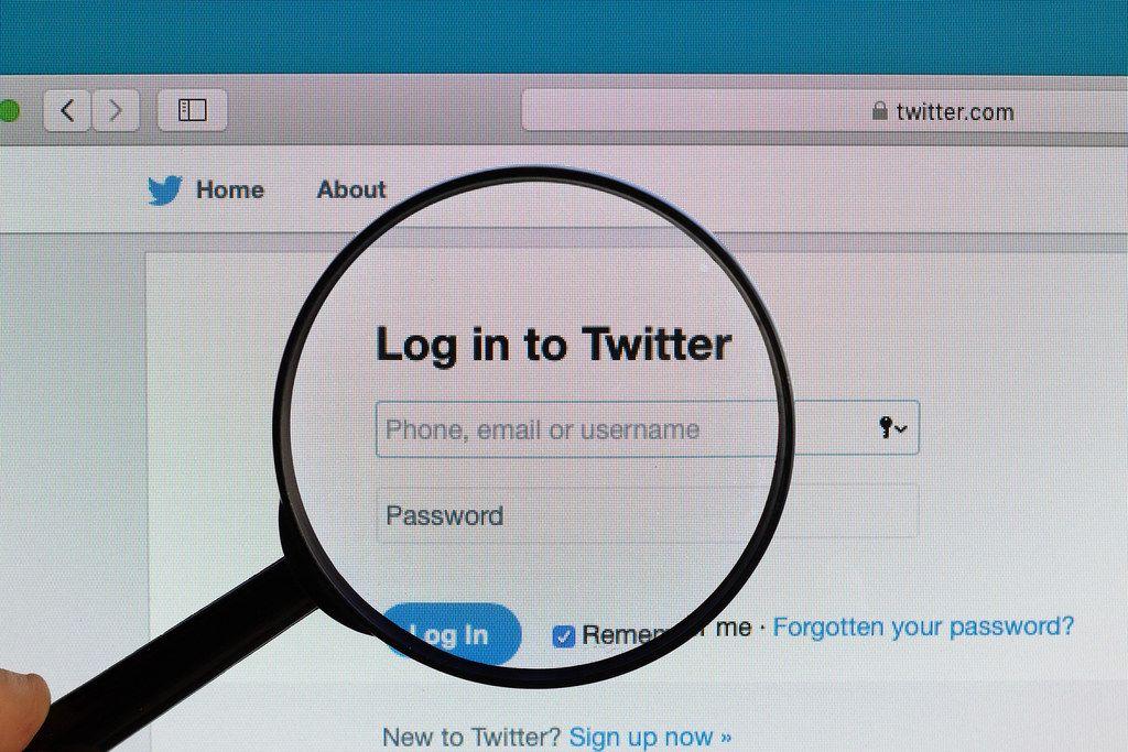 Die Anmeldeseite der Social Media Plattform Twitter, vergrößert dargestellt durch ein Lupenglas