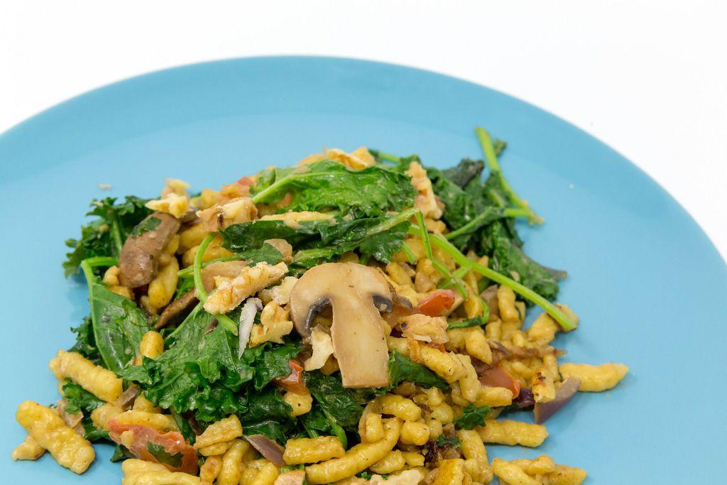 Die Hello Fresh Herbst Spätzle Pfanne mit Grünkohl, Pilzen in cremiger Soße und gerösteten Walnüssen auf einem blauen Teller in der Nahaufnahme