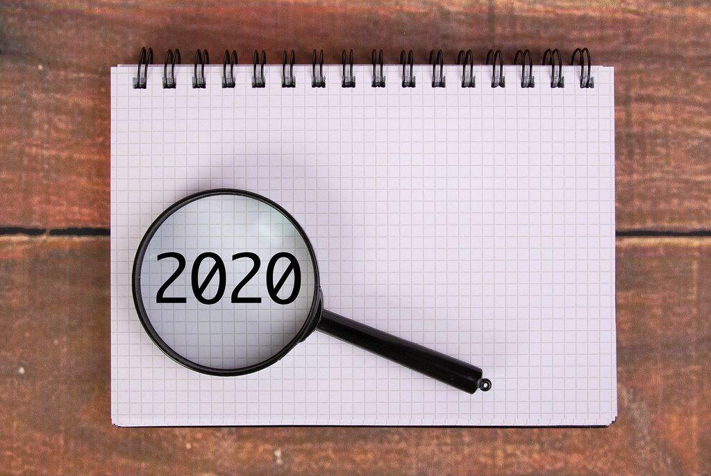 Die Jahreszahl 2020 auf einem Karoblock, vergrößert dargestellt unter einer Lupe