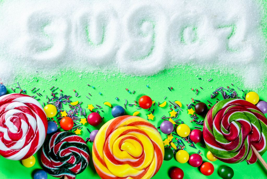 Different sweets on a green background with the inscription Sugar