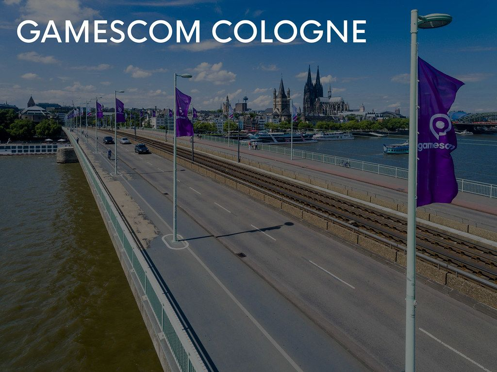 Direction to Gamescom in Cologne is accompanied by flags of the games fair, with the cathedral in the background