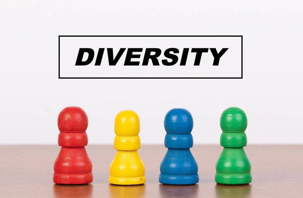 Diversity concept with four pawn figurines on table