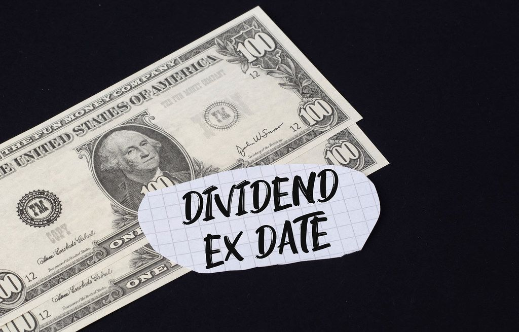 Dividend Ex Date text and dollar banknotes