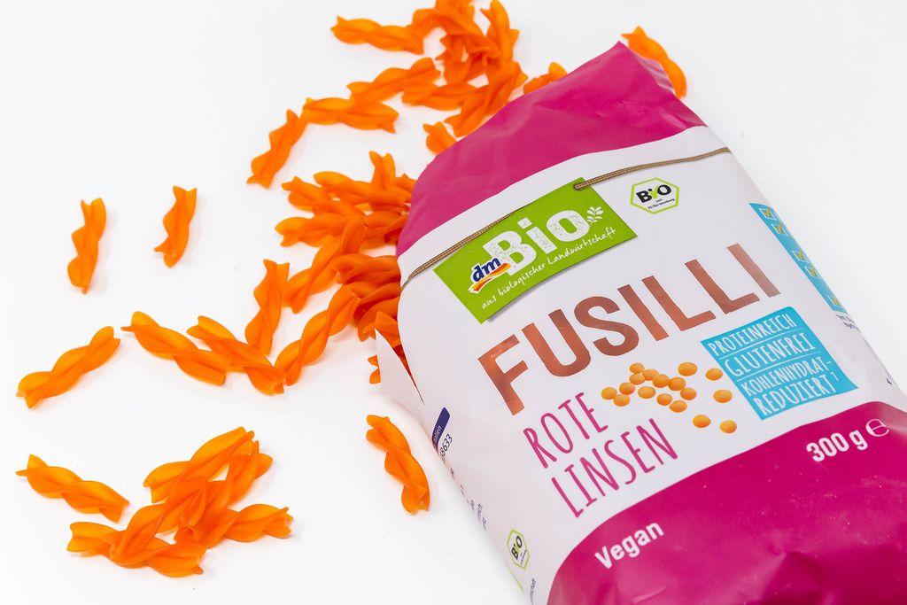 DM Bio Fusilli aus roten Linsen aus der Verpackung verschüttet auf weißem Hintergrund