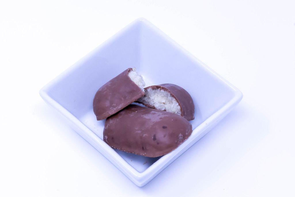 DM Bio-Vollmilch-Schokoladen-Kokosriegel in quadratischer Schale auf weißem Hintergrund