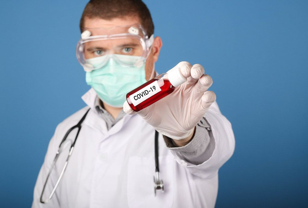 Doctor holding blood sample tube with Covid-19 text on blue background