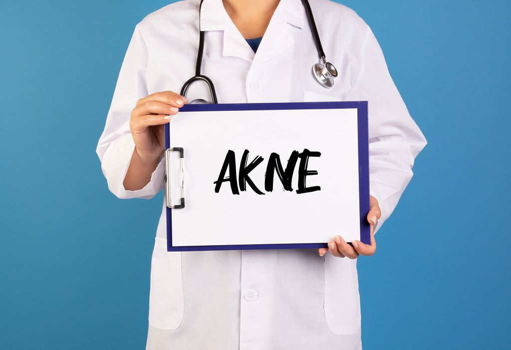 Doctor holding clipboard with Akne text