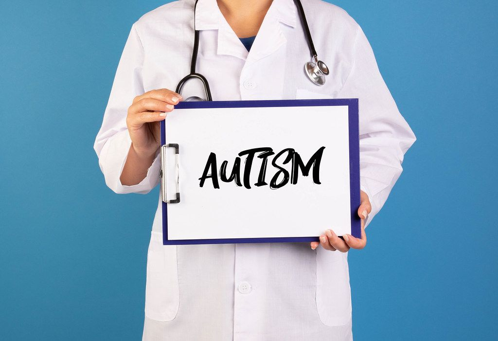Doctor holding clipboard with Autism text
