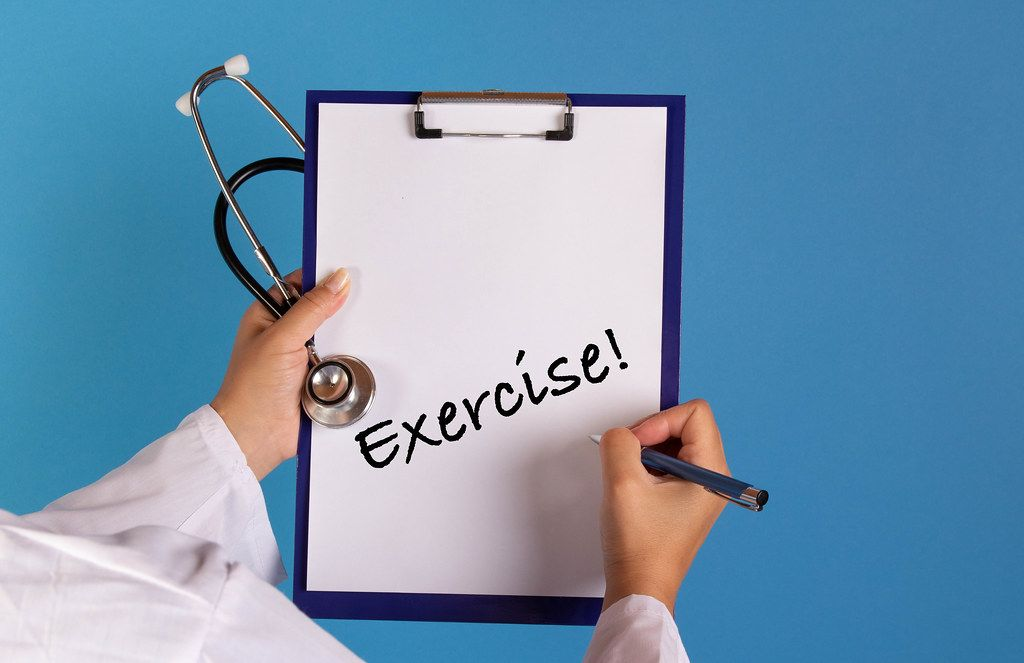 Doctor holding clipboard with Exercise text