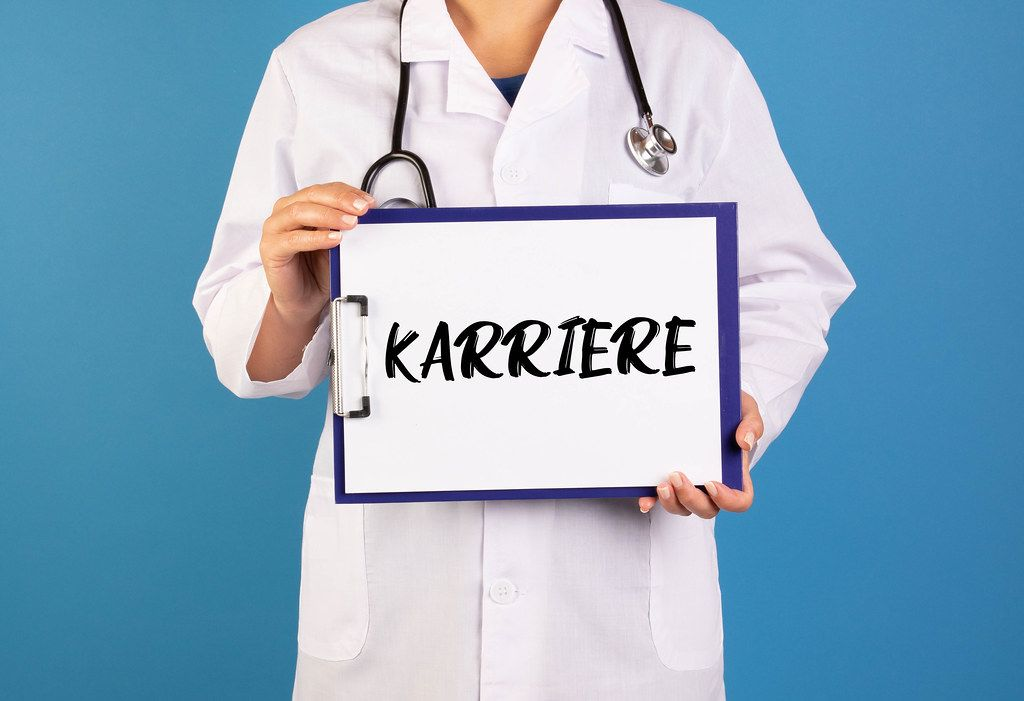 Doctor holding clipboard with Karriere text