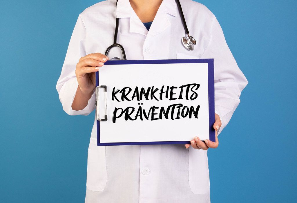 Doctor holding clipboard with Krankheitsprävention text