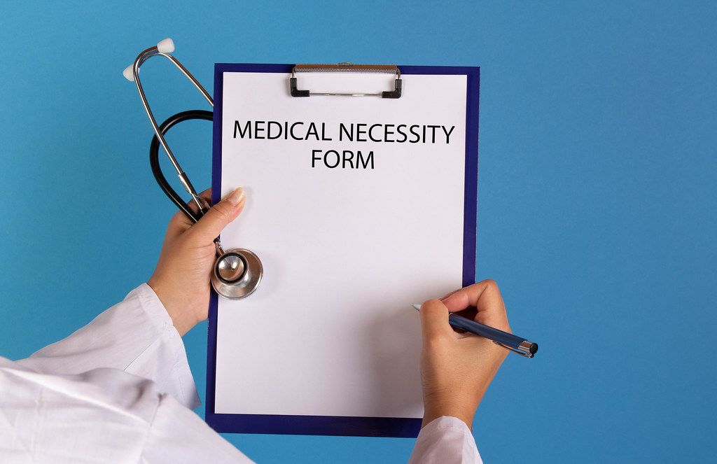 Doctor holding clipboard with Medical necessity form text