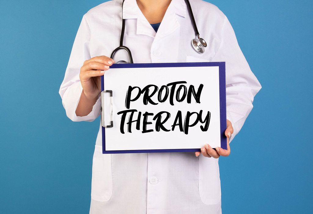 Doctor holding clipboard with Proton Therapy text