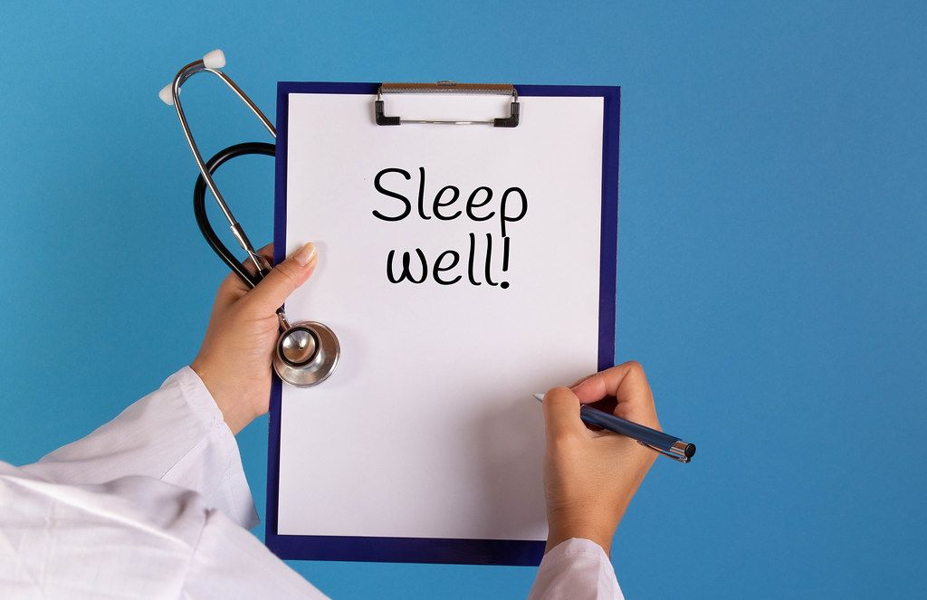 Doctor holding clipboard with Sleep well text