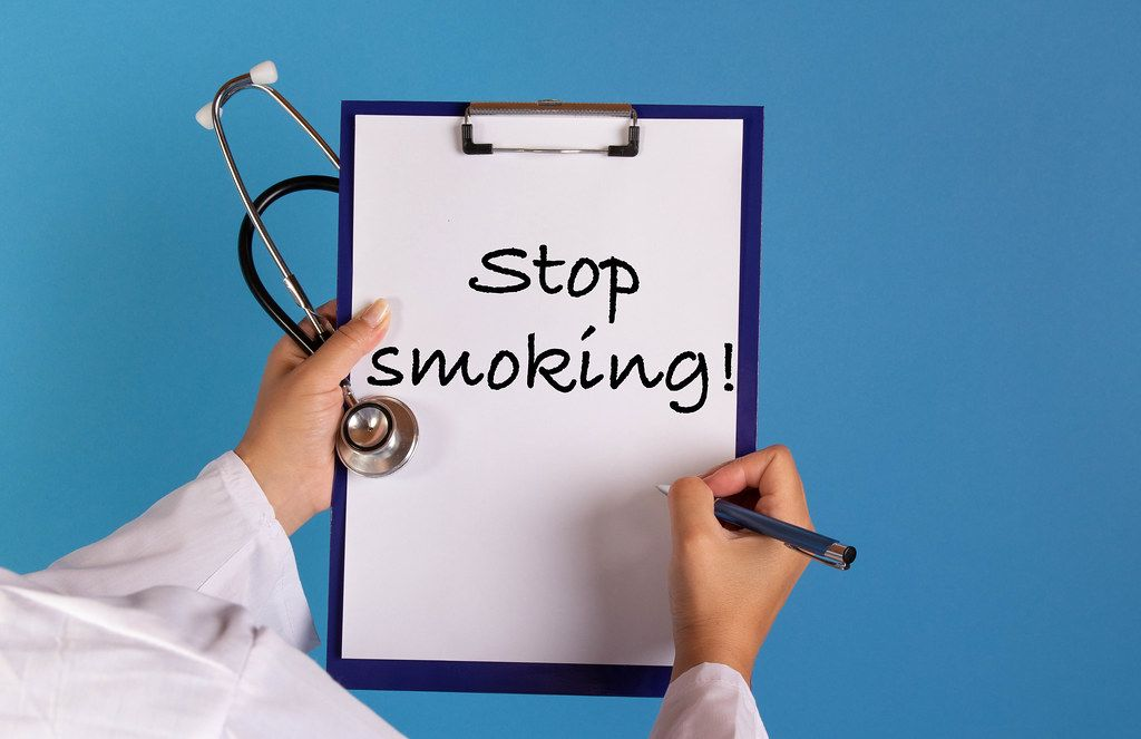Doctor holding clipboard with Stop smoking text