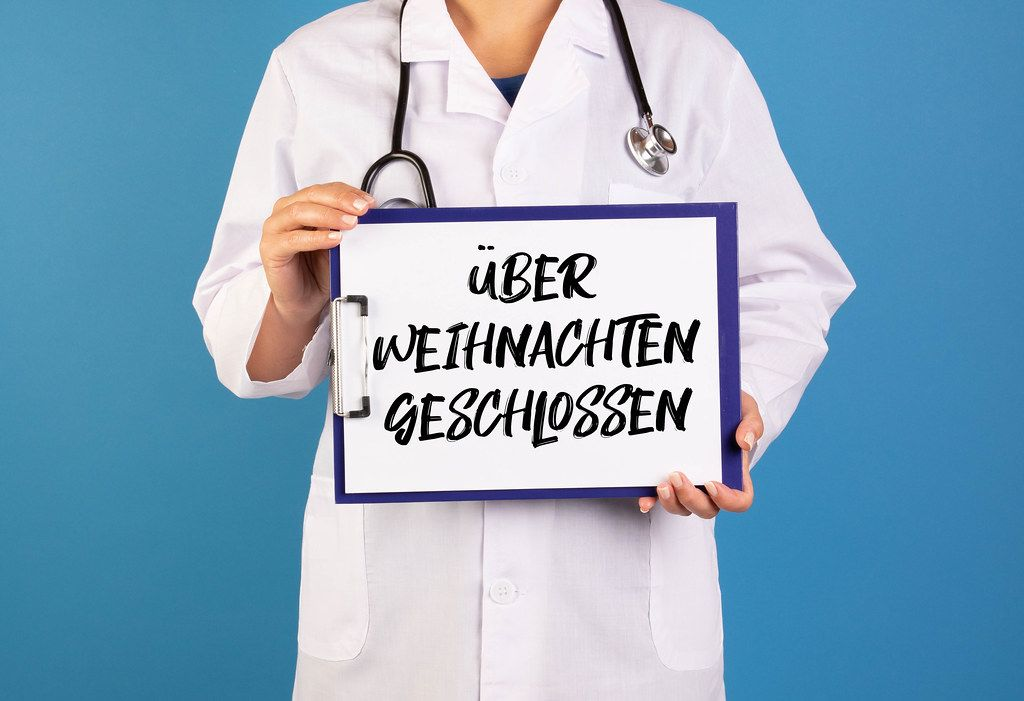 Doctor holding clipboard with über Weihnachten geschlossen text