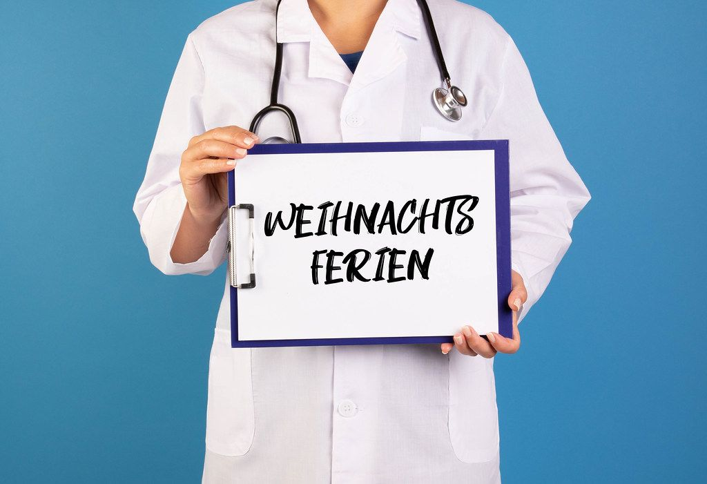 Doctor holding clipboard with Weihnachts Ferien text