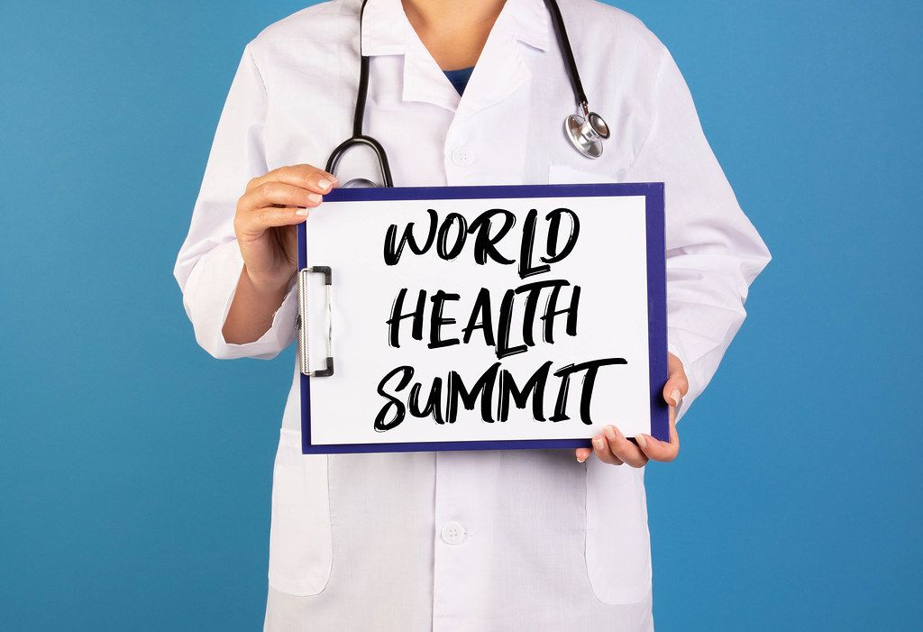 Doctor holding clipboard with World health summit text