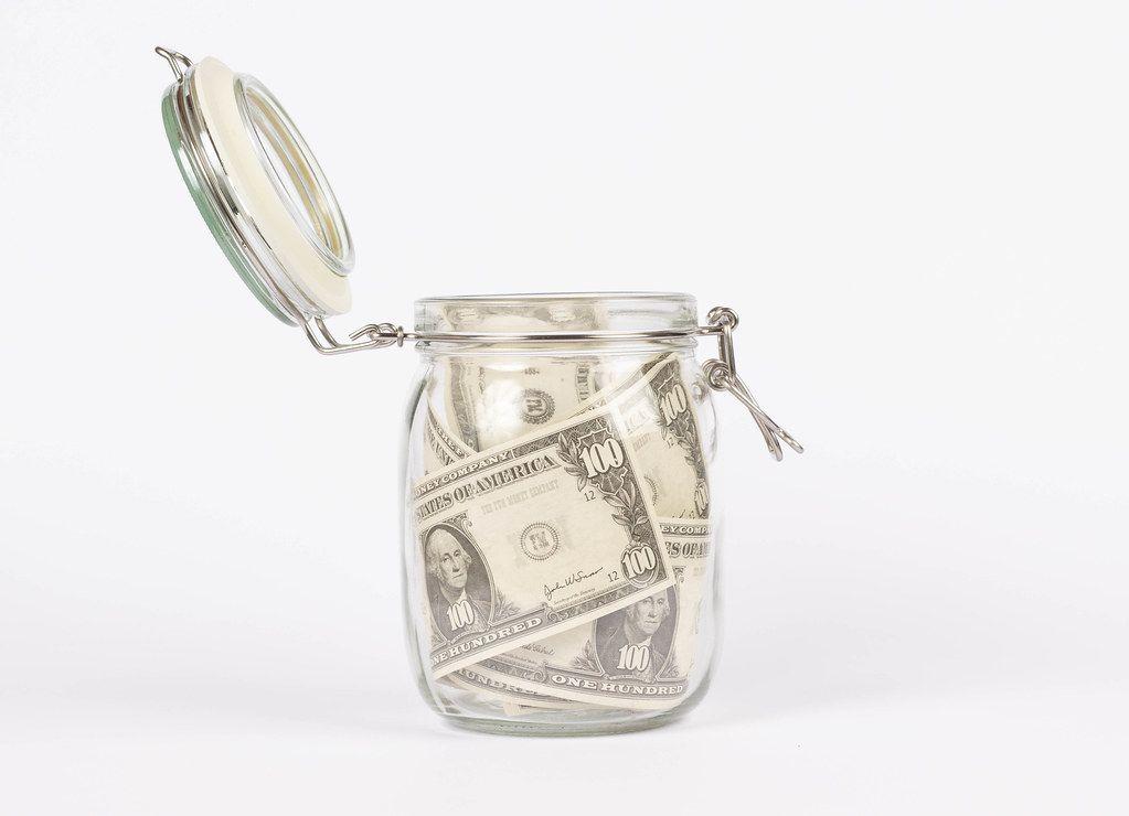Dollar bills in glass jar on white background
